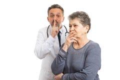 A fatura do doutor cala o gesto atrás do paciente foto de stock royalty free