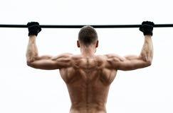 A fatura do homem do músculo levanta na barra horizontal contra o céu Fotografia de Stock