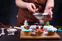 Fatura dos deleites da festa natalícia Mulher que polvilha o pó do açúcar no de fotografia de stock royalty free