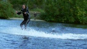 A fatura mais wakeskier do homem feliz assina pelas mãos durante o movimento no lago atrás do barco filme