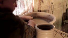 A fatura tradicional da cerâmica, próxima acima do ` s do oleiro entrega dar forma a uma bacia no giro pela argila filme