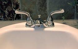Faucet ванной комнаты на раковине с плиткой задней части темноты Стоковая Фотография