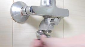 Faucet ванны reparing, вывинчивающ гайку на пропускающем влагу шланге ливня, паяющ ремонты и концепцию DIY акции видеоматериалы