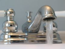 Faucet. Close-up of old-fashioned looking chrome and porcelain faucet, with water running out of it royalty free stock photo