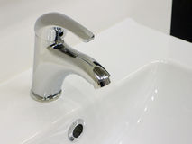 Faucet. Elegant chrome faucet on clean and brilliant white sink Stock Photography