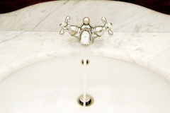 Faucet. Details of the flowing water faucet and elegant sink Royalty Free Stock Photography