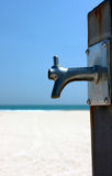 Faucet. Water tap sand beach stock images