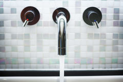 Faucet in Bathroom with Running Water Stock Images