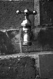 Faucet. Black and white metal faucet on a wall of bricks Stock Photo