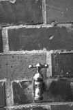 Faucet. Black and white metal faucet on a wall of bricks Royalty Free Stock Image