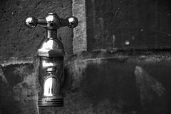 Faucet. Black and white metal faucet on a wall of bricks Royalty Free Stock Photography