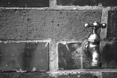 Faucet. Black and white metal faucet on a wall of bricks Stock Photography