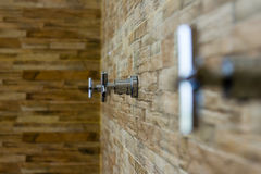 Faucet on brick wall background Stock Photo