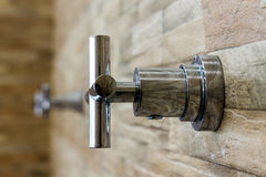 Faucet on brick wall background Stock Image