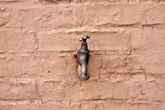 Faucet de água em uma parede foto de stock