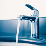 Faucet with flowing water. Blue tone Royalty Free Stock Image