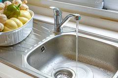 Faucet with a flowing water. Kitchen faucet with a flowing water Royalty Free Stock Images