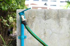 Faucet and green water hose Royalty Free Stock Image
