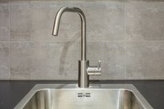 Faucet in kitchen. Close up of modern faucet and ceramic sink in kitchen royalty free stock photo