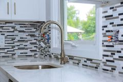 Faucet and kitchen sink with brick wall. Faucet and kitchen faucet and countertop detail sink with brick wall stock photos
