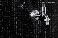Faucet. Modern design home bathroom Faucet on black tile Royalty Free Stock Photography
