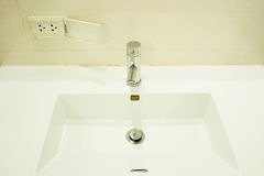 Faucet nearly plug outlet to dangerous Stock Images