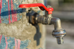 Faucet On Old Blue Painted Wall. Red Handle Water Tap Outdoor Background. Save Water Concept. Stock Photo