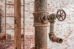 Faucet and pipe with ladder on red brick wall. Old industrial faucet against distressed brick wall with ladder and wood beam royalty free stock photo