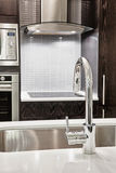 Faucet and sink in modern kitchen. Elegant faucet and sink in island counter of modern kitchen royalty free stock photos