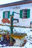 Faucet in the snow in front of an old farmhouse royalty free stock photos