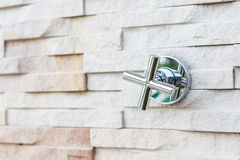 Faucet steel on stone wall Royalty Free Stock Images