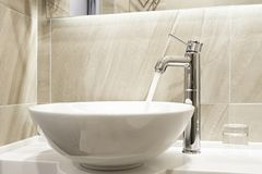 Faucet and water flow. In bathroom royalty free stock photo