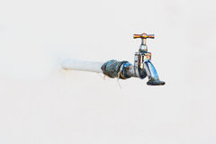 Faucet on white wall Stock Photography
