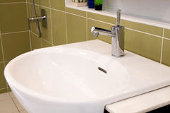 Faucet with white wash basin with ceramic tile background Royalty Free Stock Photo