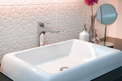 Faucet with white wash basin with ceramic tile background Stock Photo