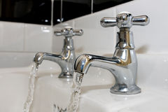 Faucets on the bath tub with running water Stock Image