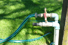 Faucets and Hoses. Two faucets and a hose in a garden stock photography