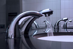 Faucets and sink. Water running down from faucet Stock Photos