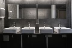 Free Faucets With Washbasin In Public Restroom In Grey Colors Royalty Free Stock Image - 135955996