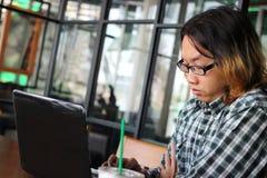 Faule junge asiatische Arbeitskraft, die Laptop an Arbeitsplatz des modernen Büros verwendet stockfotografie
