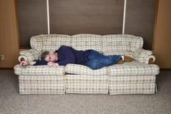 Fauler müder Mann, der schläft und ein Schläfchen hält Stockfotos