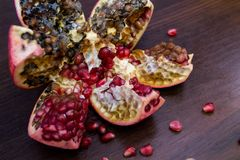 Fauler, verdorbener, polierter roter Granatapfel auf einem Holztisch mit Samen lizenzfreies stockfoto