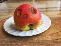 Faules Apple mit einem lustigen Gesicht Lizenzfreies Stockbild