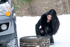 Fault car in the winter. Young beautiful girl trying to repair t. He car, engine repair Royalty Free Stock Image