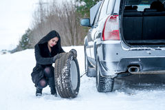 Fault car in the winter. Young beautiful girl trying to repair t. He car, engine repair Royalty Free Stock Images