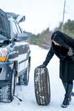 Fault car in the winter. Young beautiful girl trying to repair t. He car, engine repair Stock Photo