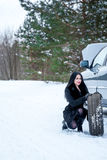 Fault car in the winter. Young beautiful girl trying to repair t. He car, engine repair Stock Images