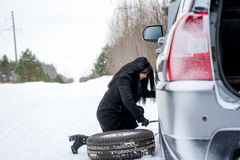Fault car in the winter. Young beautiful girl trying to repair t. He car, engine repair Stock Photos