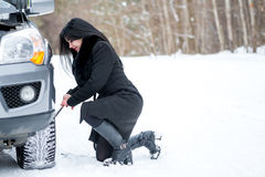 Fault car in the winter. Young beautiful girl trying to repair t. He car, engine repair, tire change Royalty Free Stock Photos