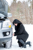 Fault car in the winter. Young beautiful girl trying to repair t Royalty Free Stock Photos